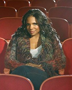 Audra McDonald seated in a performance hall